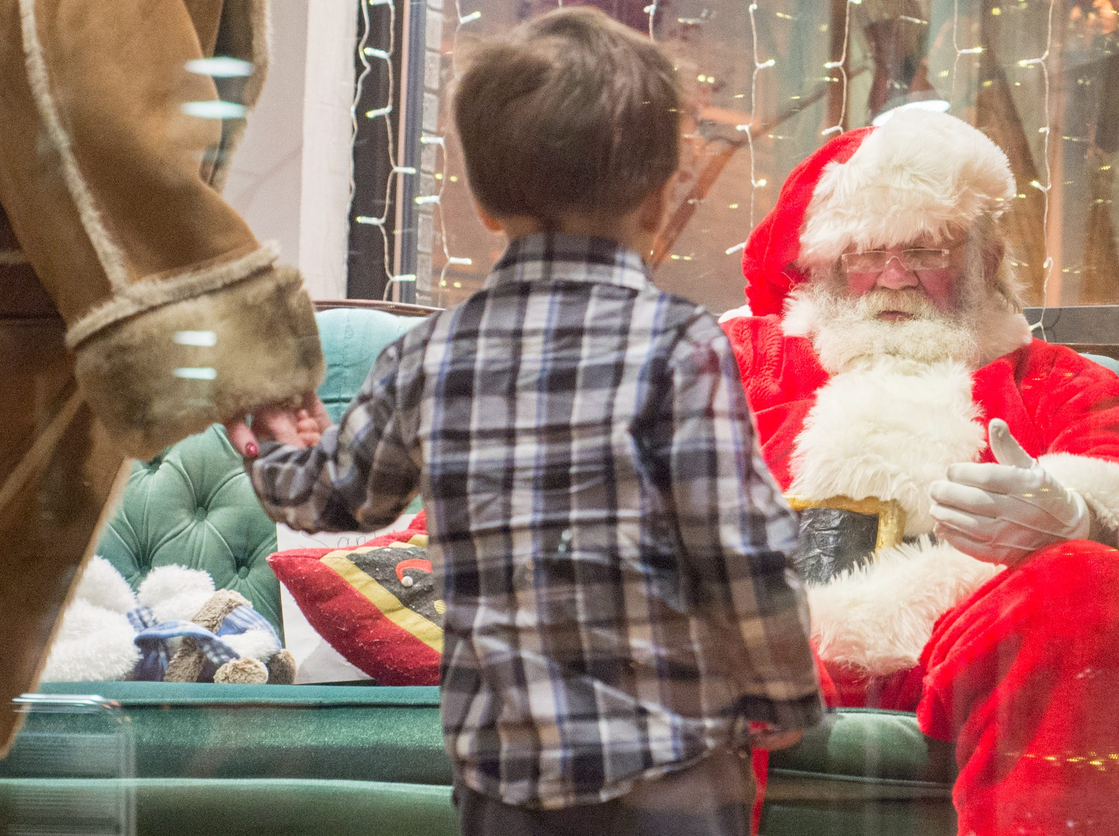 Aiden Seals meets Mr. Claus during the Santa on the Square event presented by Historic Downtown Gallatin at 106 Public Square on Saturday, Dec. 22.