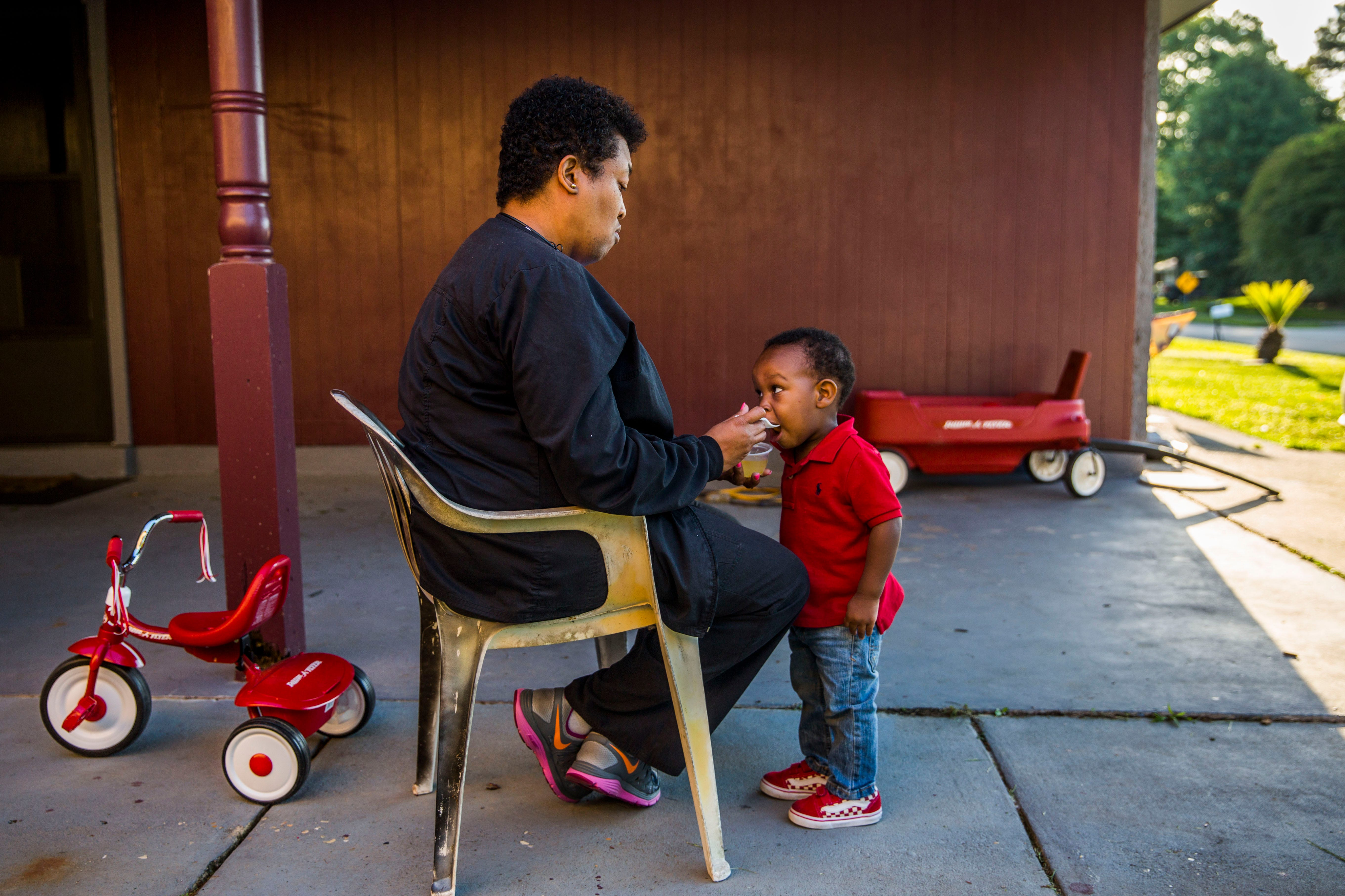 Felicia Robinson feeds Kason, now two-years-old, outside of his Baton Rouge home. After Kason's mother, Kizzy London, died from surgical complications at Jolie Plastic Surgery in December 2017, Robinson and other close family friends rallied around the young boy to help care for him.