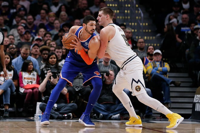 New York Knicks center Enes Kanter (00) tries to drive against Denver Nuggets center Nikola Jokic (15) in the second quarter at the Pepsi Center.