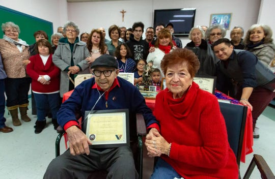 World War II veteran Albert Rel, 94, sits with his wife Sally while his family stands in the background on Saturday Dec. 29, 2018, as Rel was recognized by the Veteran's Administration in a ceremony at Immaculate Heart of Mary Catholic Church. Rel fought in WWII and was a rescue diver a Pearl Harbor.