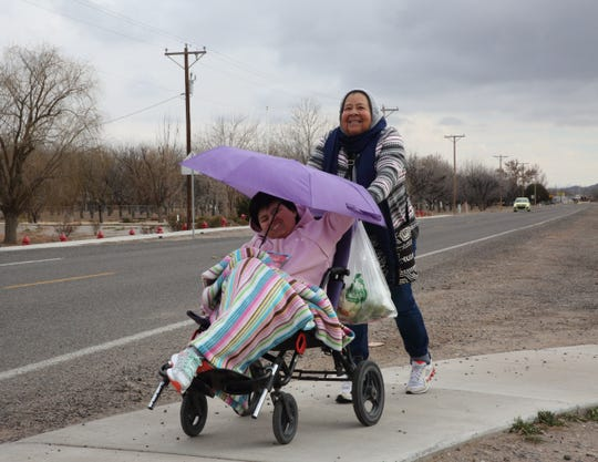 Maria De Soto, right, of Hatch pushes her daughter, Marisol Soto Gamero, who uses a wheelchair, on Jan. 2, 2019 off U.S. Hwy. 187 in Hatch, New Mexico. Snow flurries and cold weather didn't bother the two, who were on their way home after buying some groceries, De Soto said.