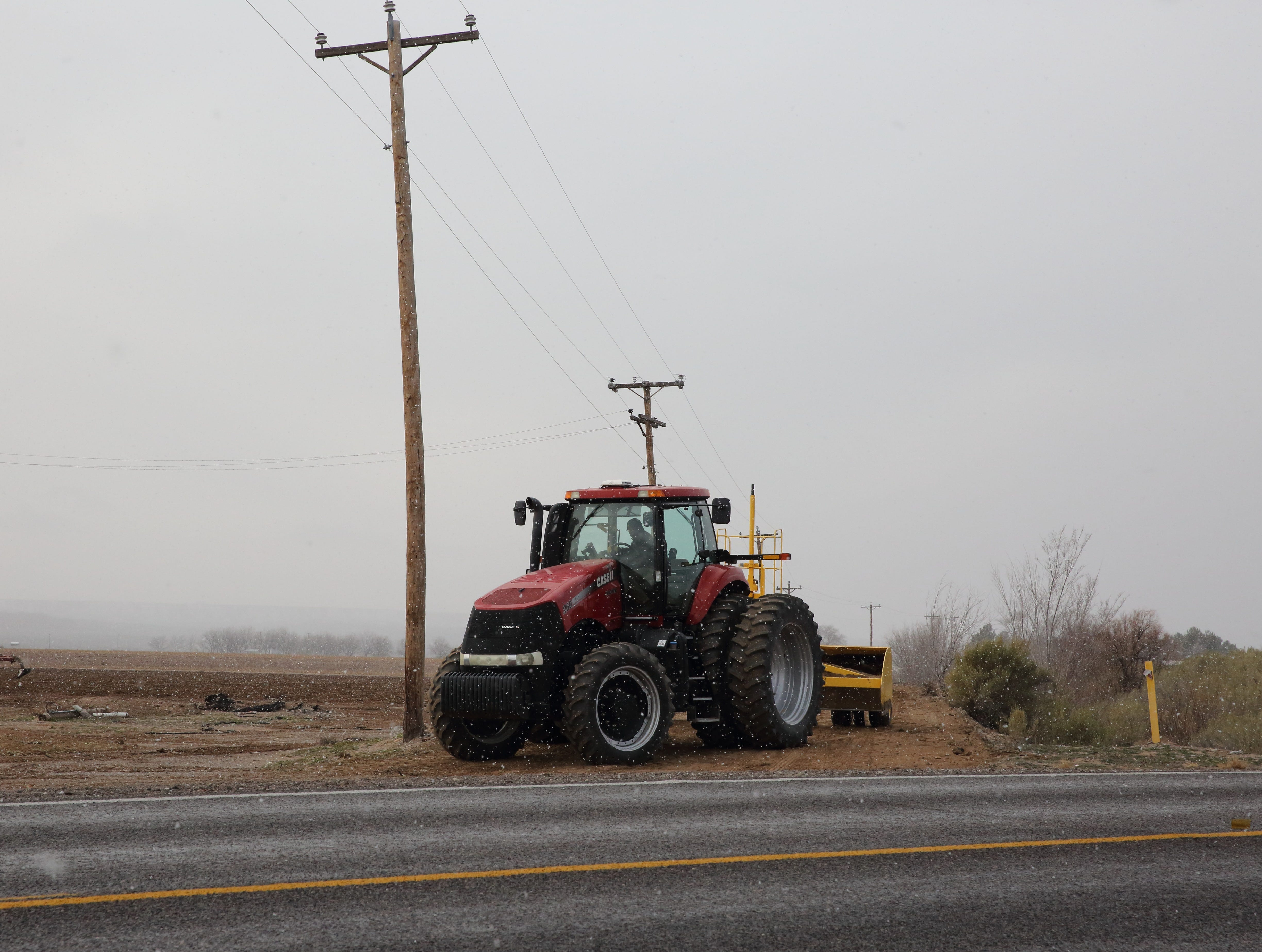 Amid snow flurries, an operator drives a tractor near a field north of Hatch, New Mexico on Wednesday, Jan. 2, 2019.