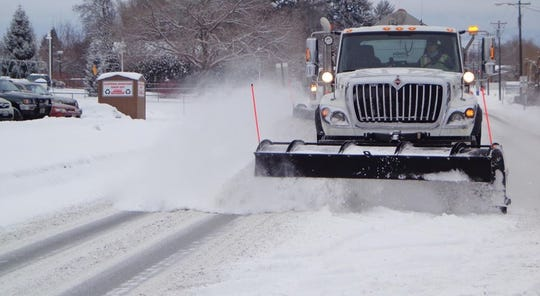 A snowplow fights flurries to keep roads open.