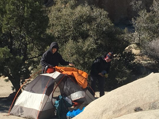 Campers take down their tent at Joshua Tree National Park Wednesday morning. Campgrounds were shut down due to a partial government shutdown that has led to a skeleton crew of rangers patrolling the park.