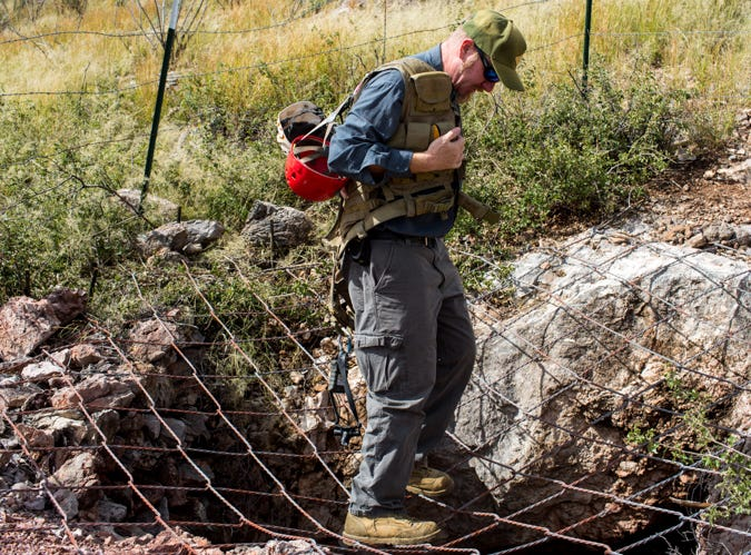 Joel Diamond, a bat biologist with Arizona Game & Fish, demonstrates the strength of spider wire over an abandoned mine shaft near Dragoon, not far from Tucson. The wire keeps people from falling into an old mine while allowing animals such as bats to easily come and go.