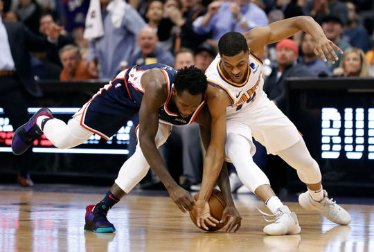 Los Angeles Clippers guard Patrick Beverley, left, and Phoenix Suns guard De'Anthony Melton battle for the loose ball during the second half of an NBA basketball game, Monday, Dec. 10, 2018, in Phoenix. The Clippers won 123-119 in overtime. (AP Photo/Matt York)