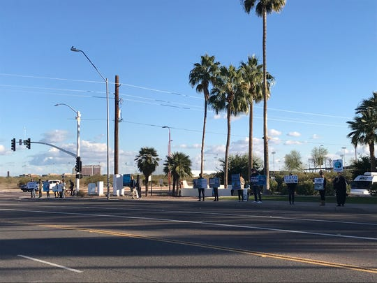 Protesters gather at an intersection near  Dolphinaris Arizona. On Dec. 30 the third of eight dolphins that the attraction has died since opening.