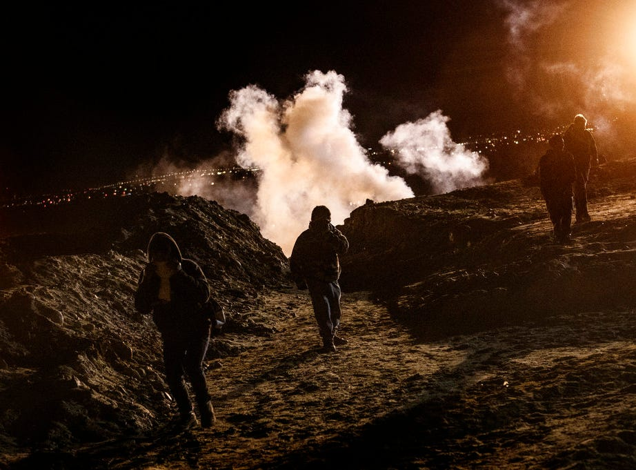 Migrants run as tear gas is thrown by U.S. Border Protection officers to the Mexican side of the border fence after they climbed the fence to get to San Diego, Calif., from Tijuana, Mexico, Jan. 1, 2019. Discouraged by the long wait to apply for asylum through official ports of entry, many migrants from recent caravans are choosing to cross the U.S. border wall and hand themselves in to border patrol agents.