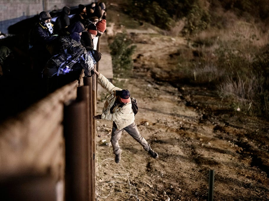 A migrant jumps the border fence to get into the U.S. side to San Diego, Calif., from Tijuana, Mexico, Jan. 1, 2019. Discouraged by the long wait to apply for asylum through official ports of entry, many migrants from recent caravans are choosing to cross the U.S. border wall and hand themselves in to border patrol agents.