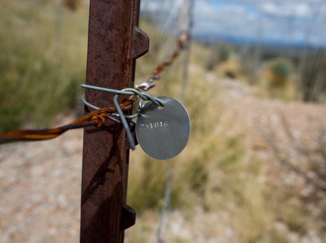 A numbering system with tags wired to fencing helps mine inspectors quickly know the type and identity of  abandoned mines like this one in Dragoon, Arizona.