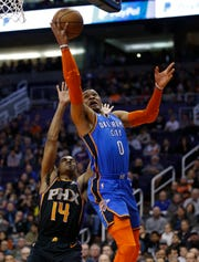 Oklahoma City Thunder guard Russell Westbrook (0) drives past Phoenix Suns guard De'Anthony Melton in the first half during an NBA basketball game, Friday, Dec. 28, 2018, in Phoenix. (AP Photo/Rick Scuteri)