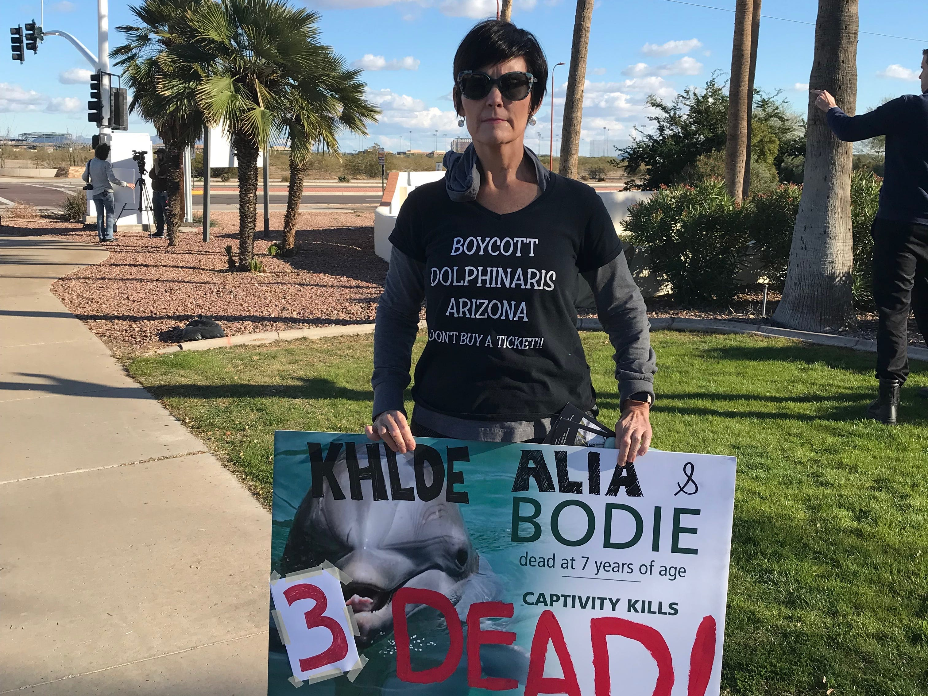 Jeanette McCourt holds a sign with the names of three dolphins that have died at Dolphinaris Arizona since it opened.