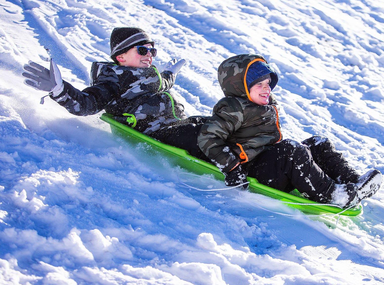 Kade Fagerud, de 6 años (izq), y su hermano Sawyer, de 5, se deslizan con deleite en una colina en Green Valley Park en Payson el 1 de enero de 2019.