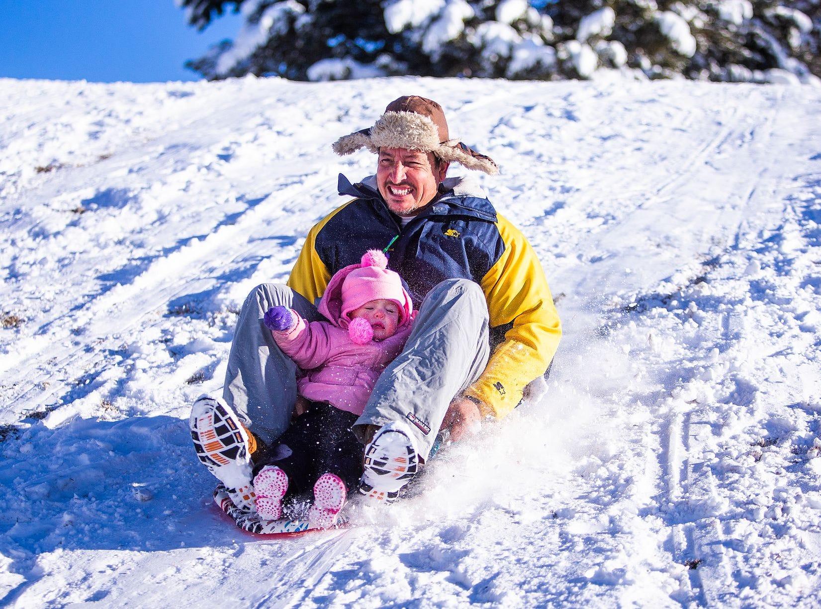 Ivan Spurlock se desliza cuesta abajo con su hija, Savannah, de 1 año, en Green Valley Park en Payson el 1 de enero de 2019.