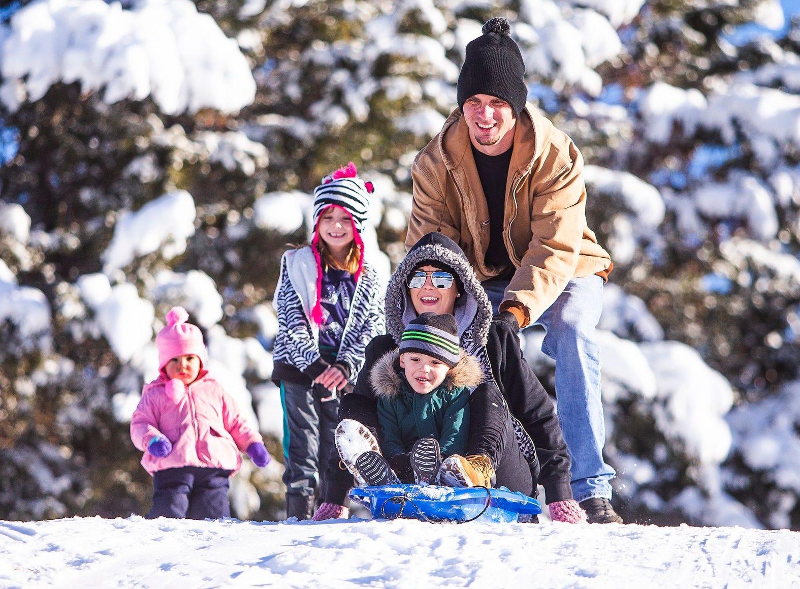 James Papa de Phoenix empuja a su esposa, Ashley, y a su hijo, Dylan, de 4 años, a una colina nevada en Green Valley Park en Payson el 1 de enero de 2019.