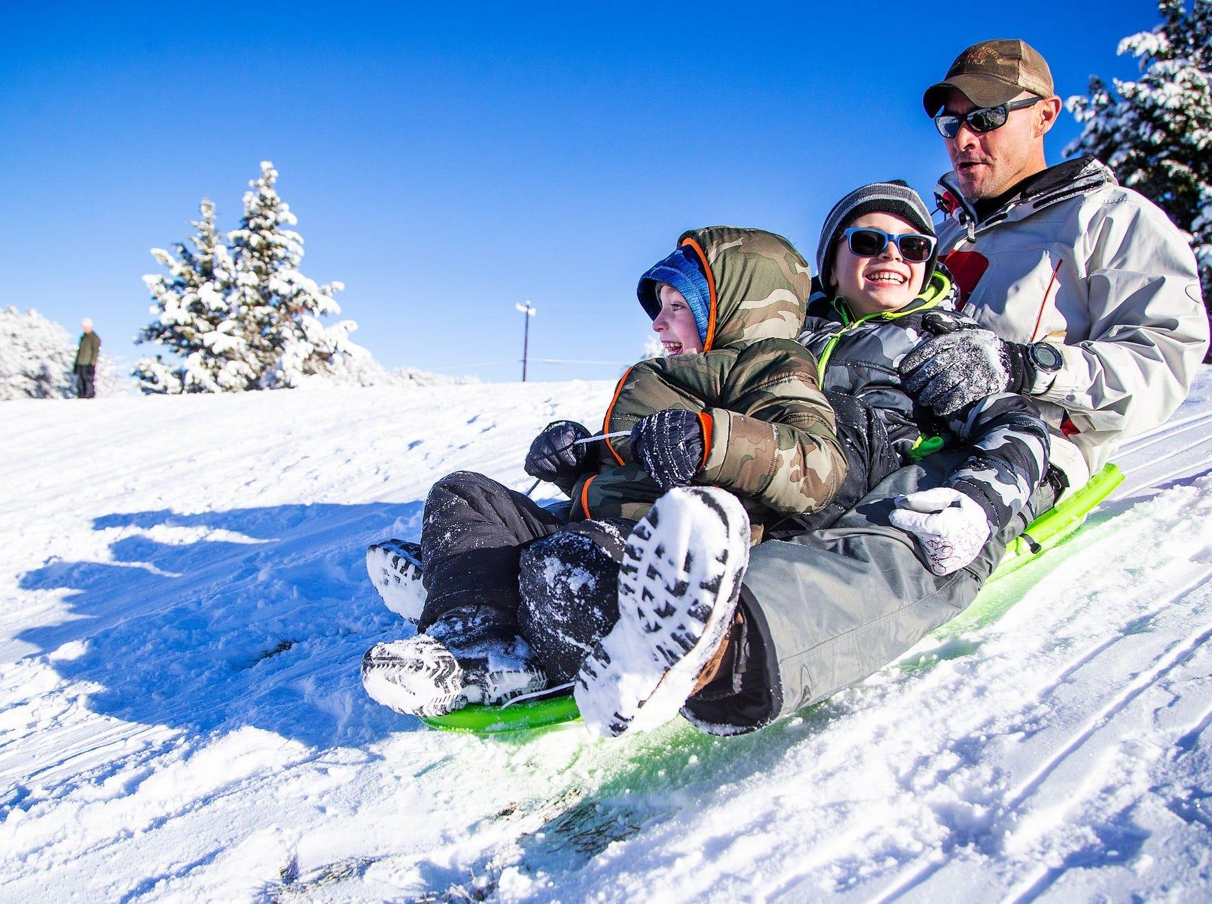 Tadd Fagerud y sus hijos, Sawyer, de 5 años (frente), y Kade, de 6 (medio), se deslizan cuesta abajo mientras disfrutan de la nevada en Green Valley Park en Payson el 1 de enero de 2019.