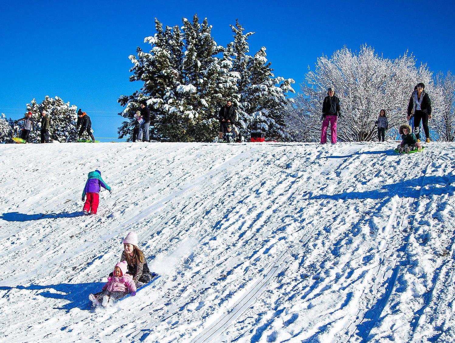 Las familias aprovechan las nuevas nevadas para deslizarse por una colina en Green Valley Park en Payson el 1 de enero de 2019.
