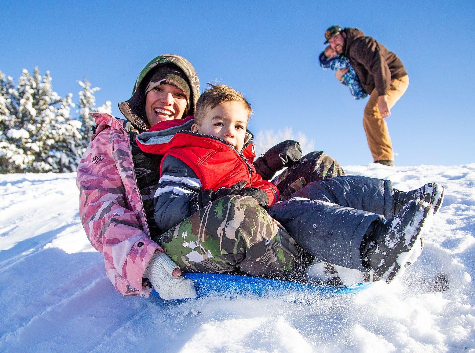 Natalie Savage y sus hijos Conor, de 2 años, y Grayson, de 4 meses, y su esposo Tyler disfrutan de la nevada en Green Valley Park en Payson el 1 de enero de 2019.