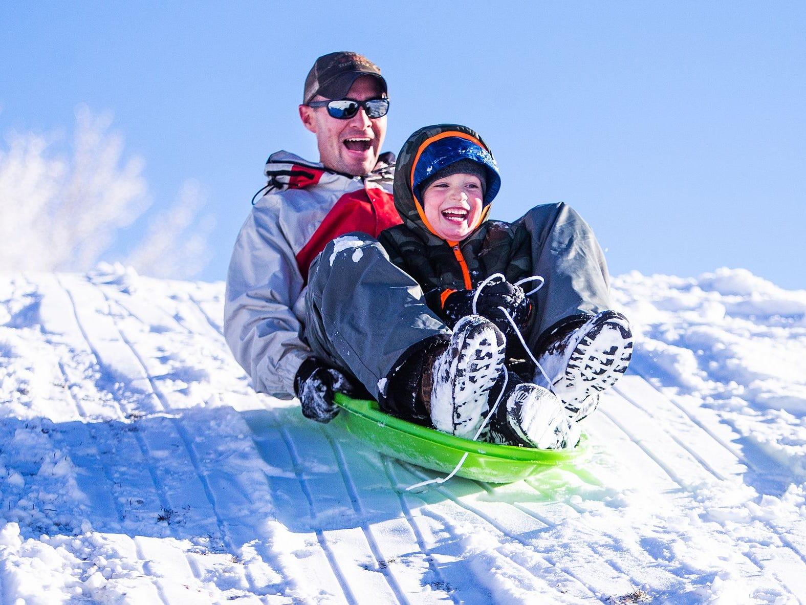 Tadd Fagerud y su hijo, Sawyer, de 5 años, se deleitan encantados mientras se deslizan cuesta abajo en una nevada fresca en Green Valley Park en Payson el 1 de enero de 2019.
