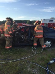 Firefighters with the Catawba Island Township Volunteer Fire Department participate in a vehicle-extraction demonstration. The department raised the amount paid to members to go on fire and EMS calls.