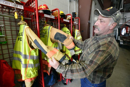 Chief Doug Crowell with the Ballville Volunteer Fire Department compares turn out gear.