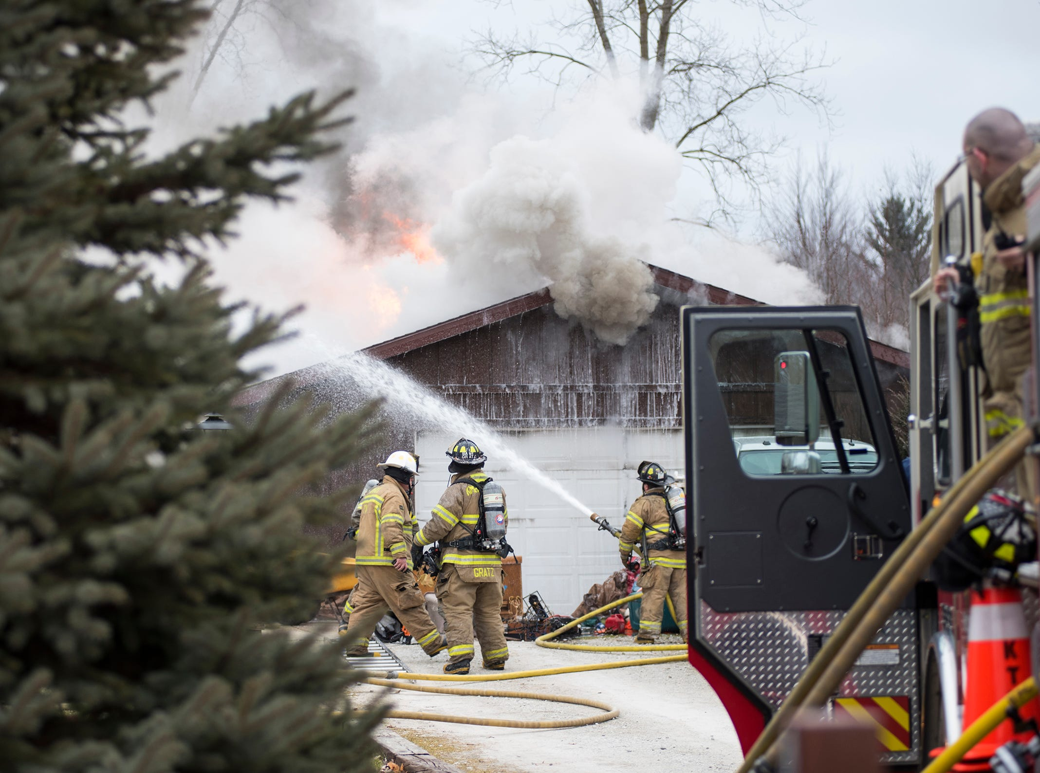 Firefighters battle a garage fire on Howard Road in Kimball Township Wednesday, Jan. 2, 2019.