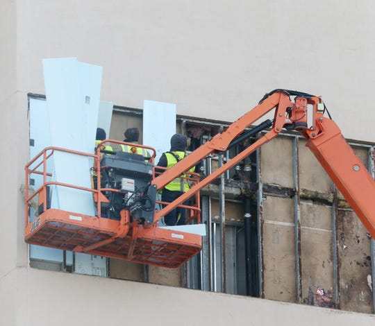 Workers repair a section of the Poughkeepsie Grand Hotel's facade that fell early Tuesday morning due to wind and rain damage on January 2, 2019.