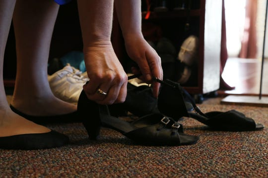Julie Donato puts on a pair of her dancing shoes before taking to the dance floor at Hudson Valley Dance Depot in LaGrangeville on December 26, 2018.