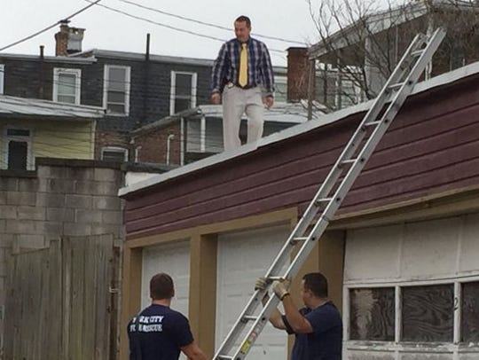 Firefighters hold a ladder for a York City Police detective as he looks on rooftops in York during a July 4 homicide investigation.