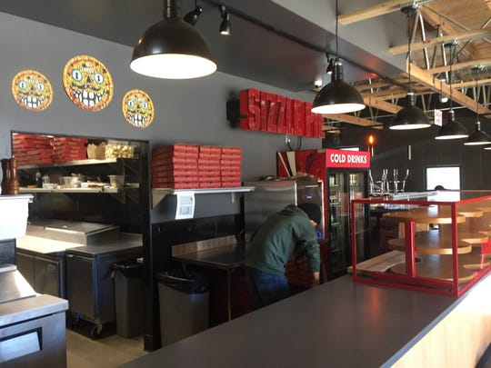 The interior of Sizzle Pie Reno that opened Jan. 4, 2019, on South Center Street, features Sizzle signatures like a marquee-inspired sign and pies grinning with menace.