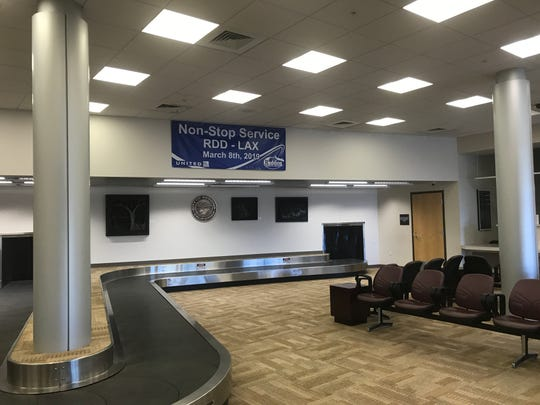 A banner announcing direct service to Los Angeles sits in the baggage pickup area at Redding Municipal Airport.