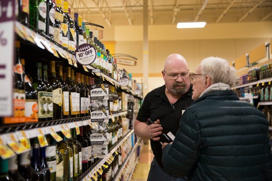 Matt Chandler, the wine steward for the South Salem Fred Meyer, helps a customer on Wednesday, Jan. 2, 2019. Chandler is celebrating his 50th anniversary with the company.