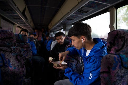 Cesar Gandara eats fries as the McKay boys soccer team boards the bus to Bend.