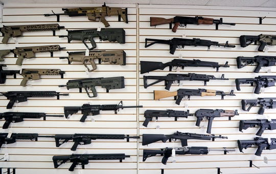 In this Oct. 2, 2018, semi-automatic rifles fill a wall at a gun shop in Lynnwood, Wash.