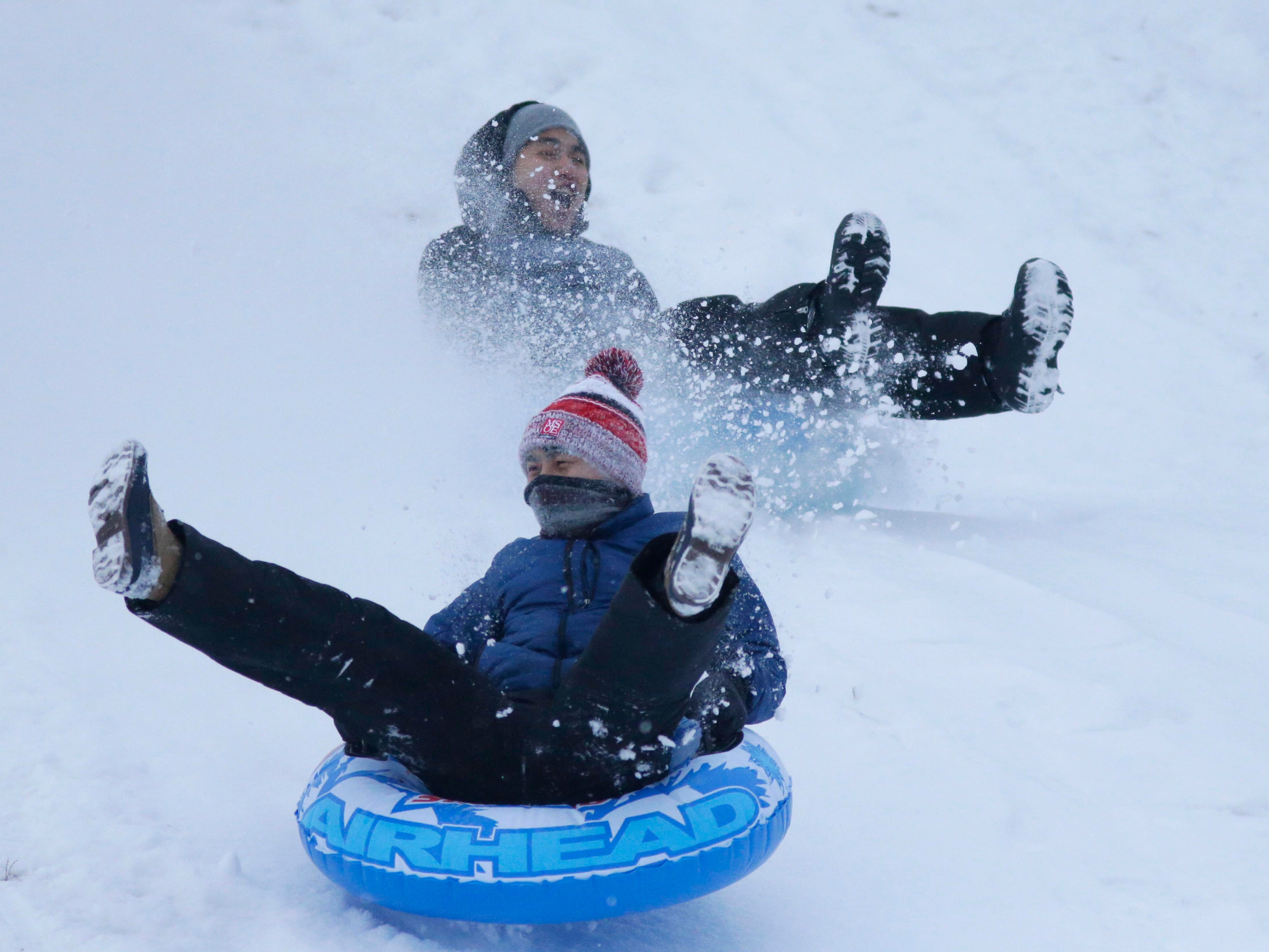 Andrew Yang, 19, and David Yang, 18, tube down Kiwanis Park, Wednesday, January 2, 2019, in Sheboygan, Wis. The two decided to get in some fun with the fresh snow.