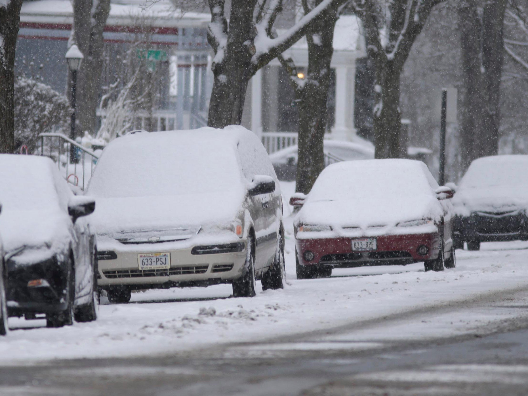 Fresh snow covers windshields on parked cars near Michigan Avenue, Wednesday, January 2, 2019, in Sheboygan, Wis.