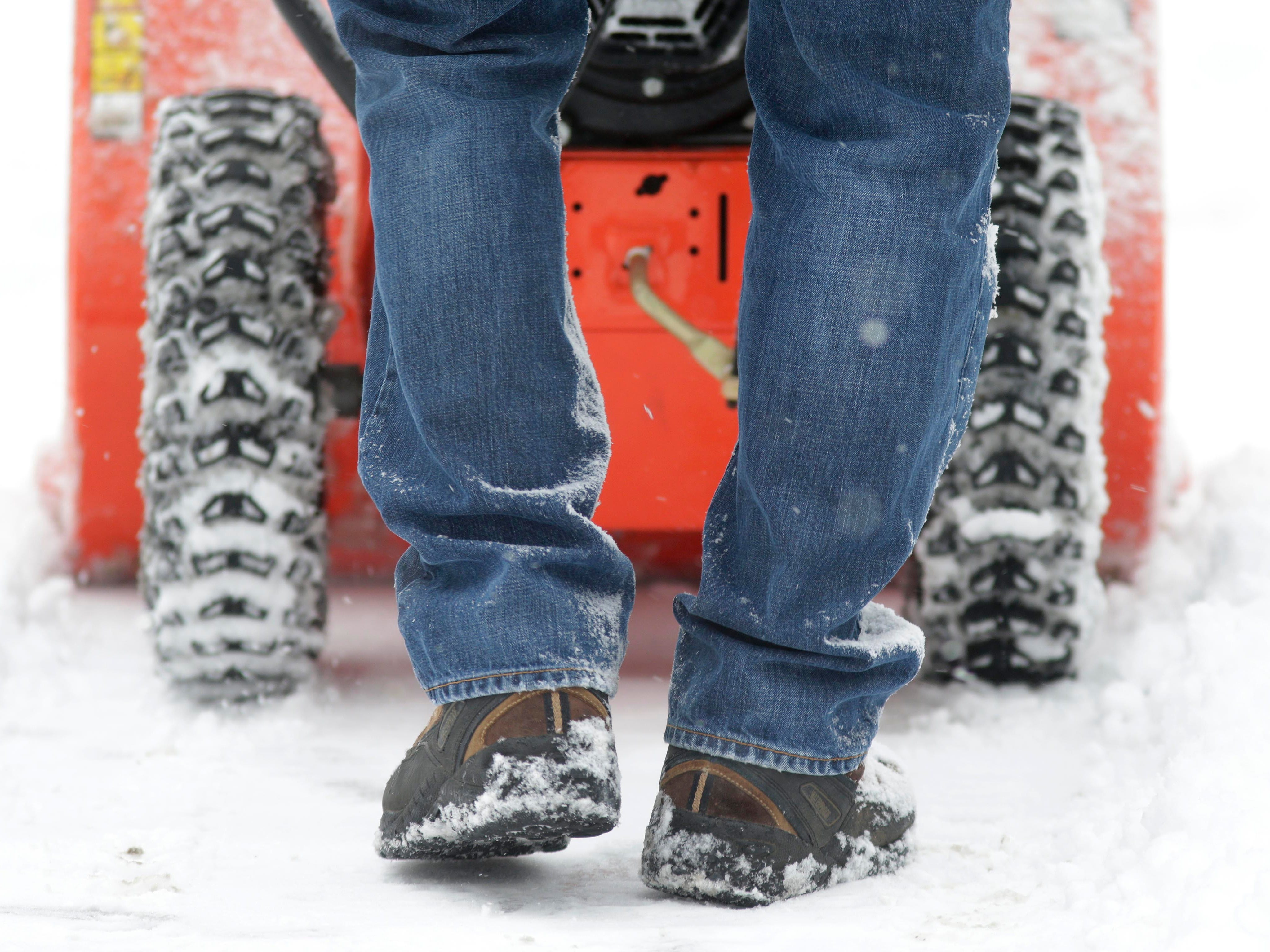 The feet of Russ Nitsch and his snowblower work to clear a sidewalk on the city's east side, Wednesday, January 2, 2019, in Sheboygan, Wis.