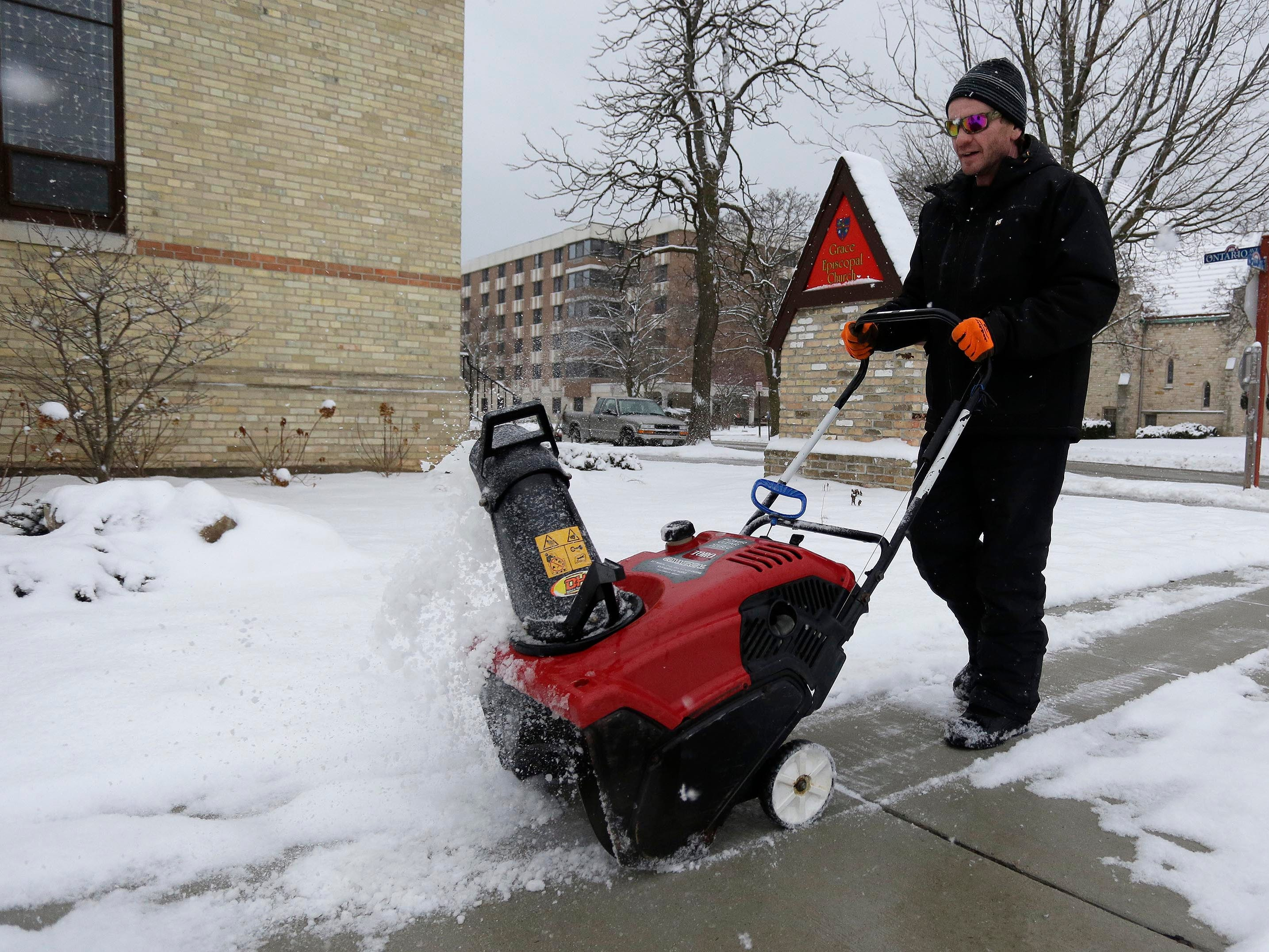 Jessie Krueger of Autumn Ridge Lanscaping in Plymouth, clears sidewalks at Grace Episcopal Church along North 7th Street, Wednesday, January 2, 2019, in Sheboygan, Wis.