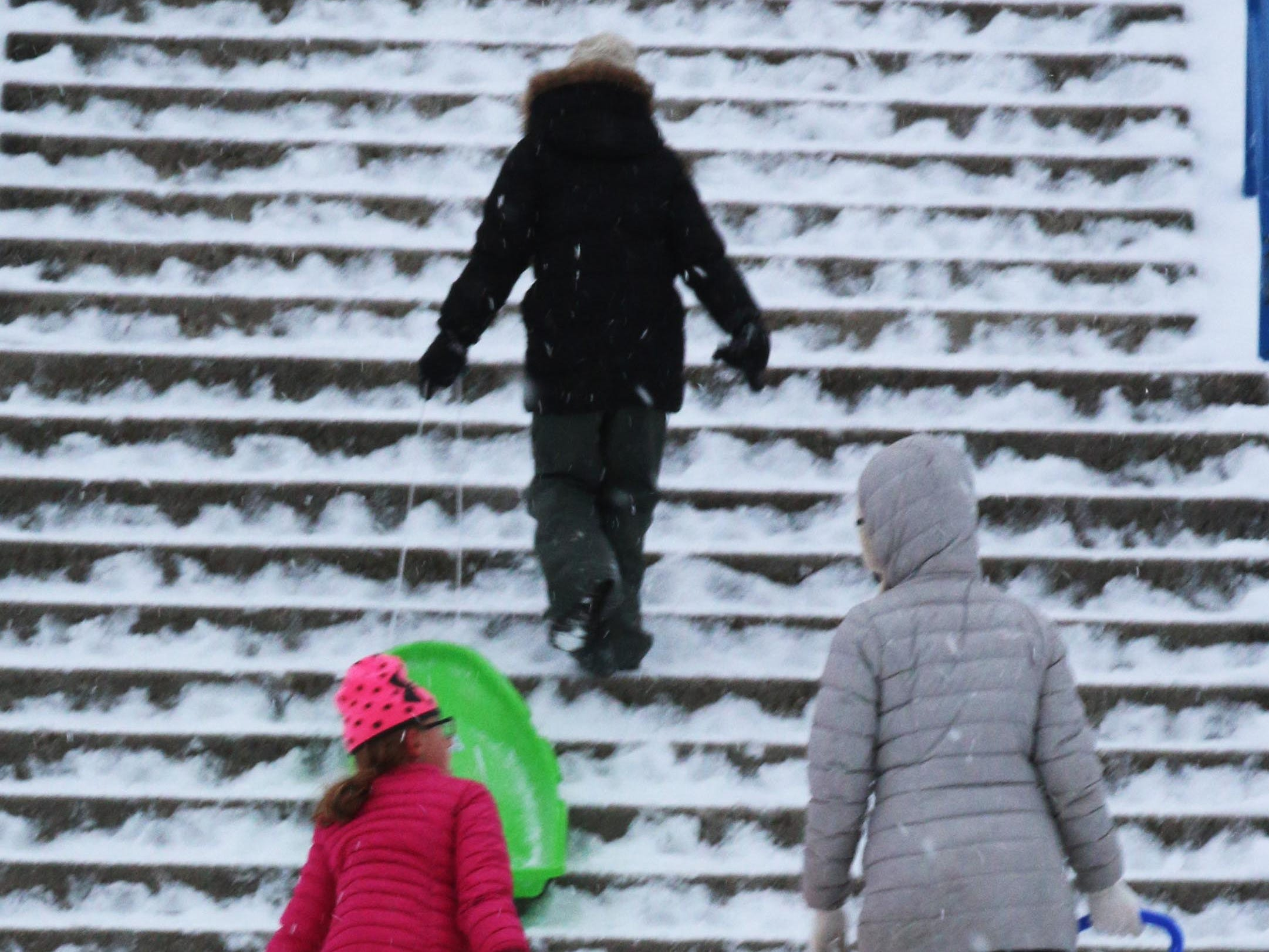 Sledders walk up the stairs at Vollrath Bowl, Wednesday, January 2, 2019, in Sheboygan, Wis.
