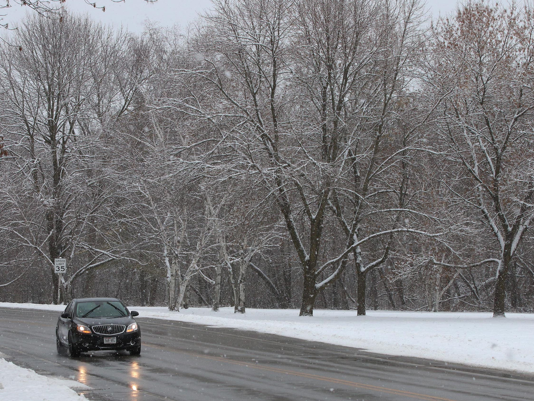 A motorist drives on county Road PP with a backdrop of snow frosted trees, Wednesday, January 2, 2019, in Kohler, Wis.