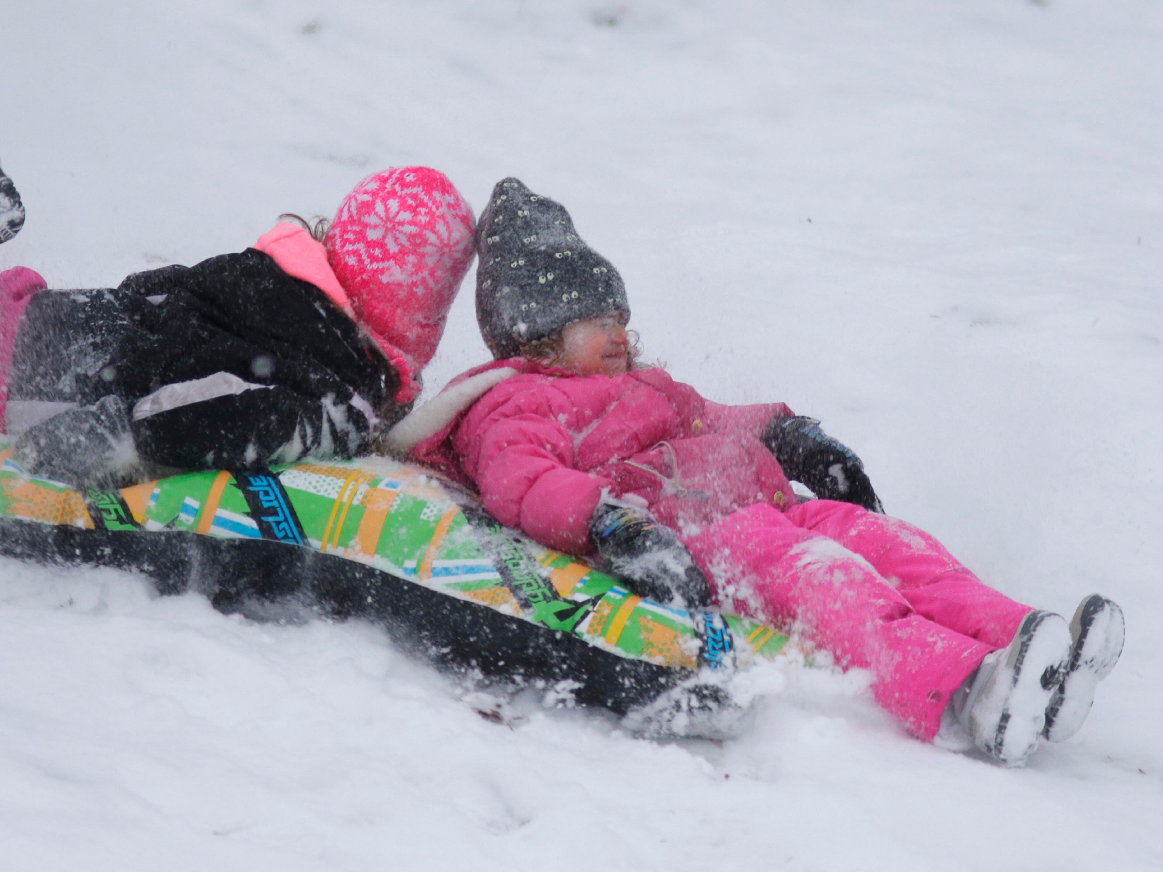 Zayna Kleppin, 7, left, and her sister Sabrina, 4, sled down the hill at Vollrath Bowl, Wednesday, January 2, 2019, in Sheboygan, Wis.