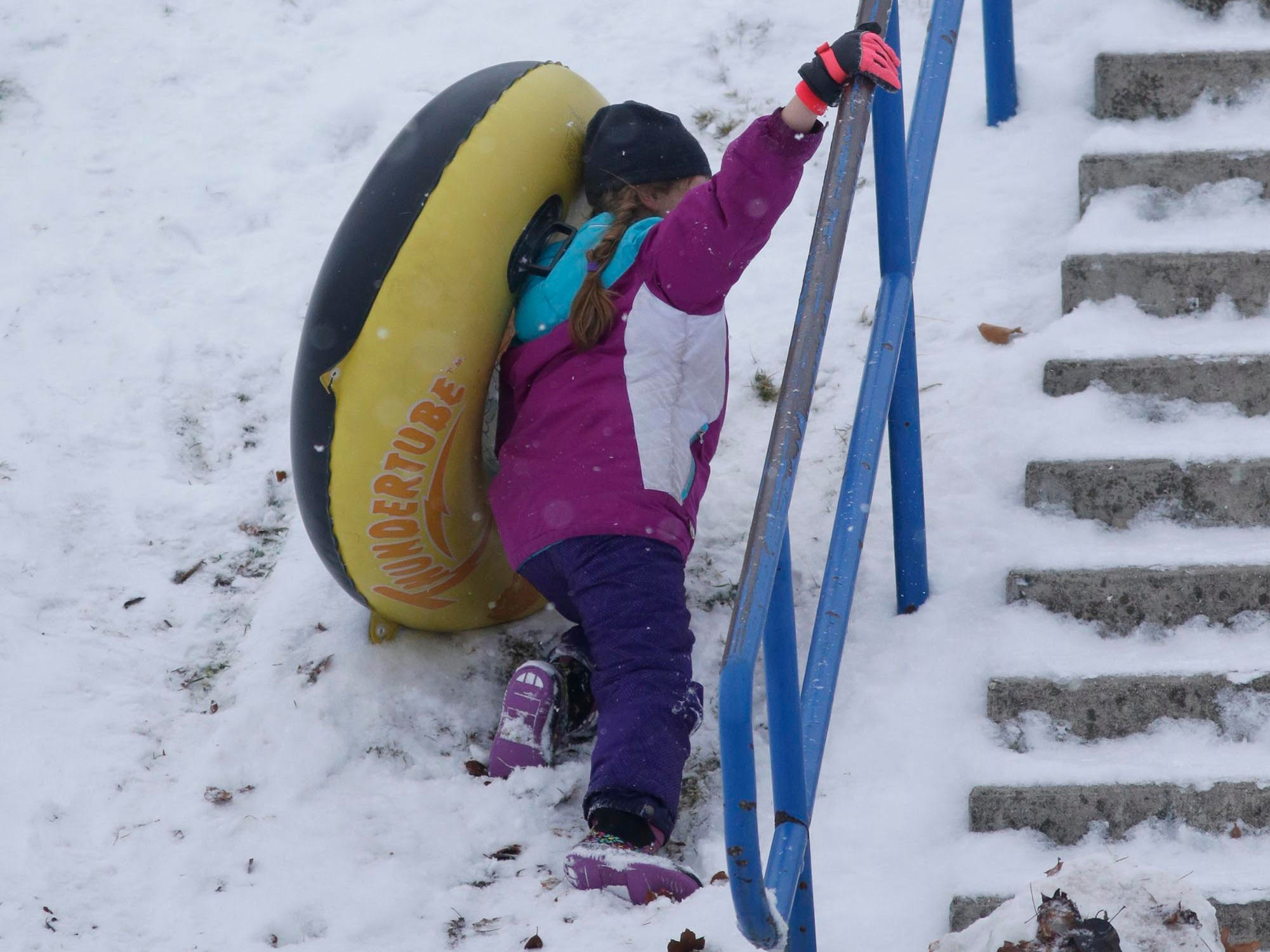 A youngster walks up the hill at Vollrath Bowl after tubing down fresh snow, Wednesday, January 2, 2019, in Sheboygan, Wis.