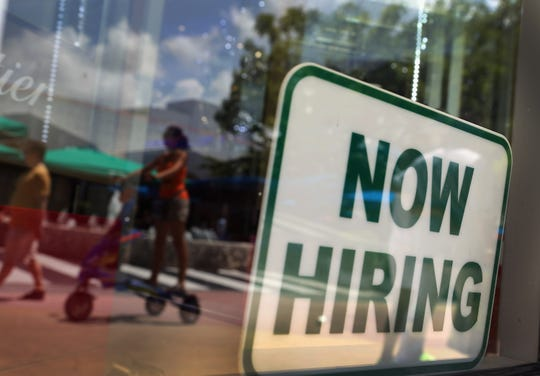 FILE: A ''Now Hiring'' sign is seen in the store front window.