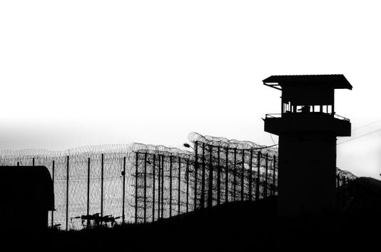 Silhouette Of Barbed Wires And Watchtower Of Prison