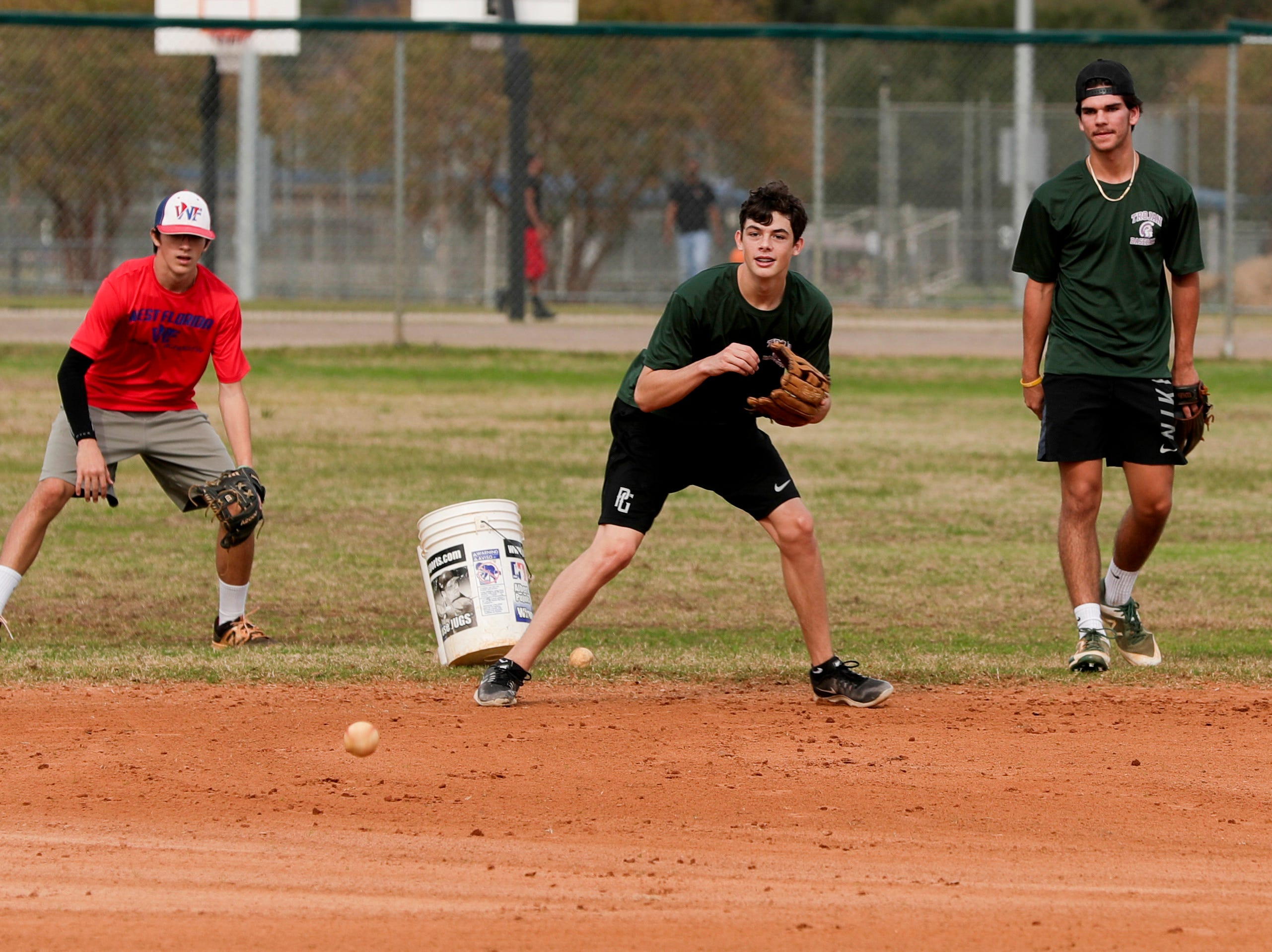 Stephen Jensen, 14, left, Tristan Harley, 15 and Connor Majors, 15, Lincoln High School baseball players, practice fielding balls at Tom Brown Park in Tallahassee as temperatures reached about 75 degrees midday Wednesday, Jan. 2, 2019.