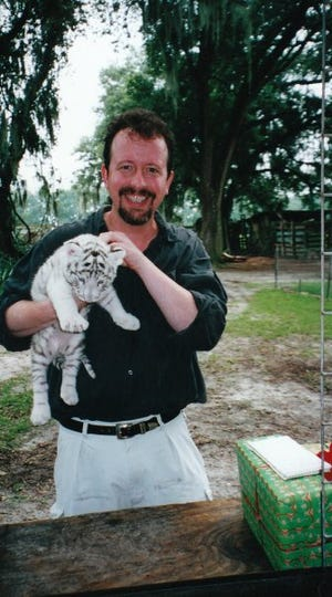 Columnist Mark Hinson holds one of white tiger cubs during a photo shoot at Savage Kingdom in the summer of 2001. The cub was a fussy model. Special to the Democrat