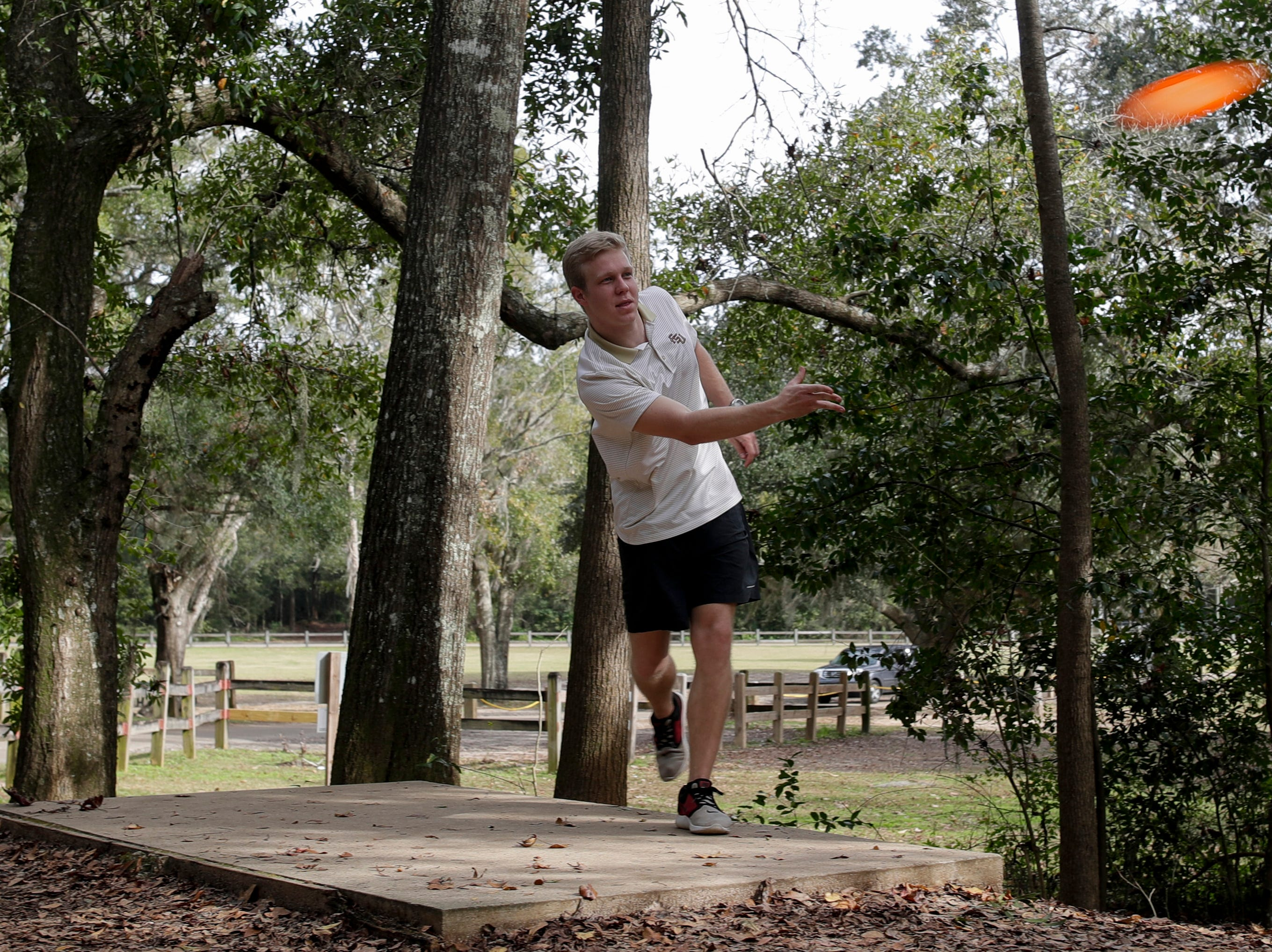 Trace Hunter tees off on a disc golf hole at Tom Brown Park as temperatures reached about 75 degrees midday in Tallahassee Wednesday, Jan. 2, 2019.