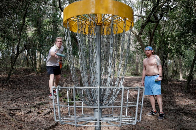 Trace Hunter, left and Greyson Laramore play disc golf at Tom Brown Park in Tallahassee as the temperature reached about 75 degrees midday Wednesday, January 2, 2019.