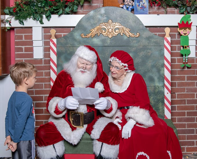 Aedan Callahan, left, shows his Christmas list to Santa and Mrs. Claus at the Tykes & Teens Festival of Trees & Lights.
