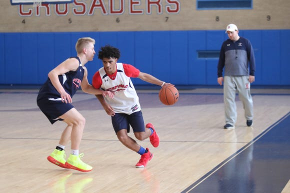 Stepinac's RJ Davis (1) works the ball as head coach Pat Massaroni watches during practice at Stepinac High School in White Plains on Wednesday, January 2, 2019.